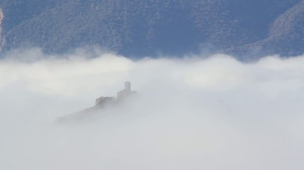 A church over a hill in the middle of a sea of fog. Time Lapse