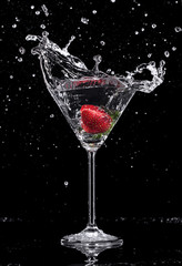 Martini drink splashing out of glass on black background