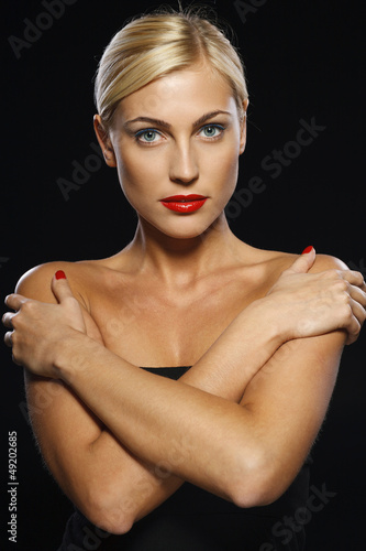 Serious woman crossed her arms, isolated over black background