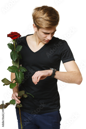 Young man holding red rose and looking at his wirstwatch