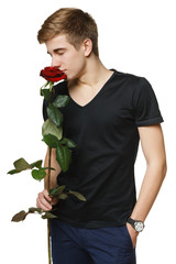 Young man smelling red rose with closed eyes