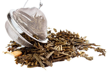Tea herbs with strainer , isolated on white