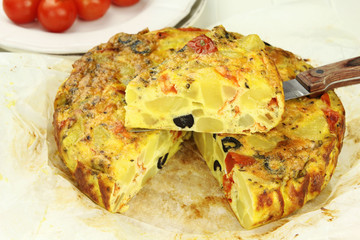 Spanish potato tortilla with black olives and tomatoes
