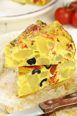 Slices of Spanish potato tortilla with black olives and tomatoes