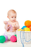 Baby plays with colored balls of yarn