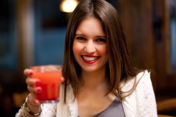 Woman drinking a cocktail in a bar