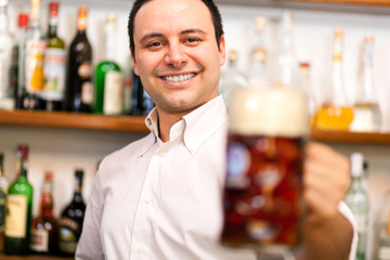 Barman offering a beer in a pub