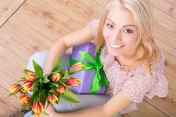 frau mit geschenk und blumen