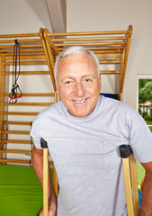 Senior mit Krücken in Turnhalle