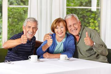 Senioren beim Kaffeetrinken halten Daumen hoch