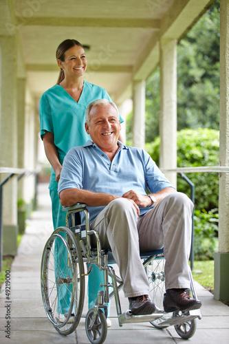 Senior im Rollstuhl mit Krankenpflegerin