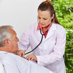 Ärztin hört alten Mann ab mit Stethoskop