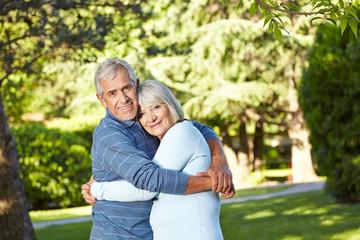 Zwei Senioren umarmen sich im Garten