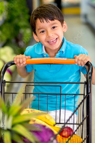 Boy playing with a shopping cart