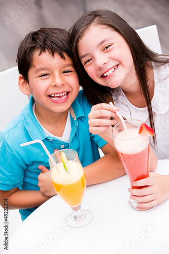 Kids drinking juice and smiling
