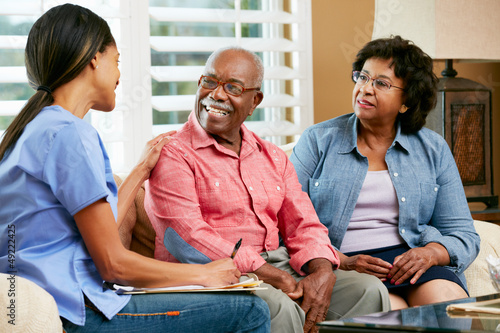 canvas print picture Nurse Making Notes During Home Visit With Senior Couple