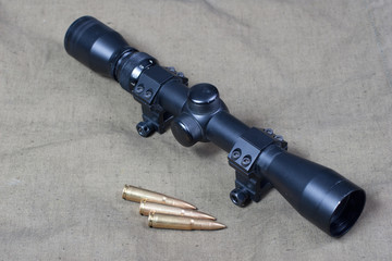 rifle scope and cartridges on khaki background