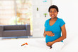 pregnant african woman sitting on bed at home