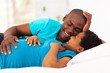 expecting african american couple lying on bed and chatting