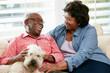 Happy Senior Couple Sitting On Sofa With Dog