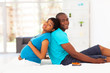 pregnant african american woman and husband sitting on bed