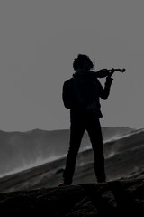 backlit violinist on bromo
