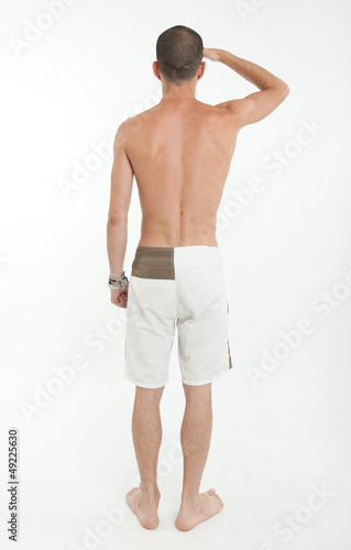 Rear view of man in swimming trunks looking far