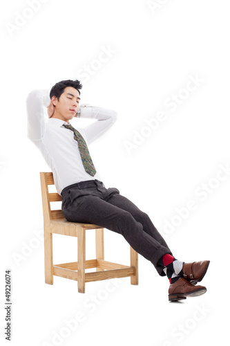 Young Asian business man sitting on the chair and fall a sleep.