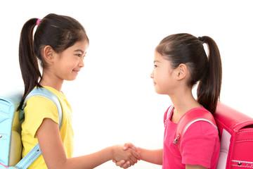 握手をして微笑む二人の女の子