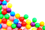 Corner border of colorful gumball candies over white