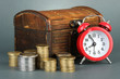 Alarm clock with coins in chest on grey background