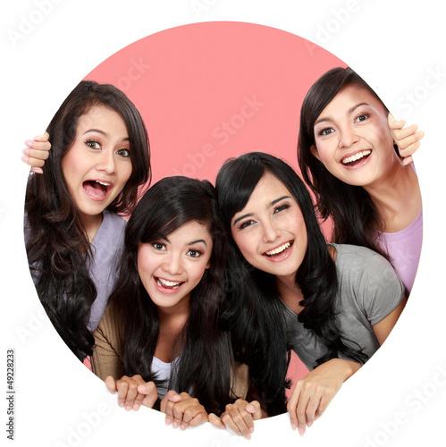 Group of beautiful women smiling peeping through circle hole