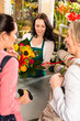 Happy women customers buying flowers sunflower bouquet