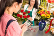 Woman customer paying flowers shop credit card