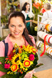 Smiling young florist woman colorful bouquet shop
