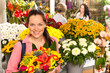 Cheerful florist woman showing colorful flowers market