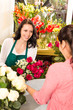 Happy florist making roses bouquet women customer