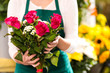 Florist hands showing red roses bouquet flowers
