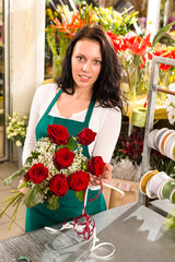Florist woman arranging flowers roses shop working