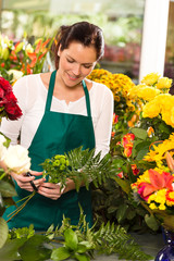 Young florist preparing flowers bouquet shop store