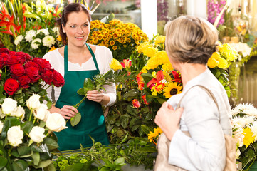 Young woman arranging flowers shop market selling