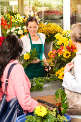 Young woman florist cutting flower shop customers