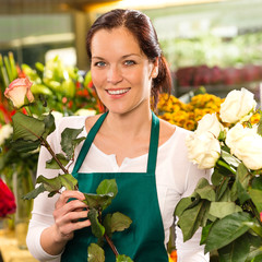 Smiling florist cutting rose flower shop woman
