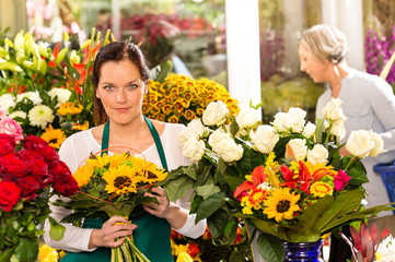 Woman florist selling sunflowers bouquet flower shop