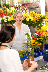 Senior woman buying plant paying flower market
