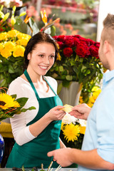 Smiling florist man customer buying flowers card