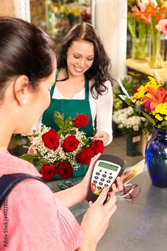 Woman florist selling flowers customer paying card