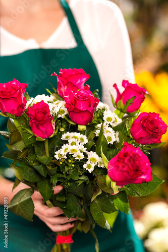 Florist woman holding red roses bouquet hands