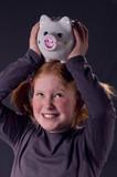 Mädchen mit Sparschwein auf dem Kopf