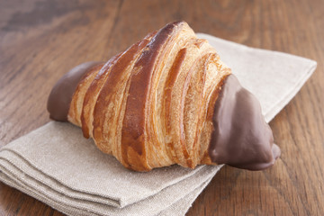 Chocolate croissant on rustic table